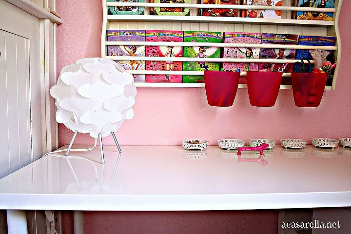 Plastic buckets hang from the bookcase and make a perfect place to store pens and pencils.