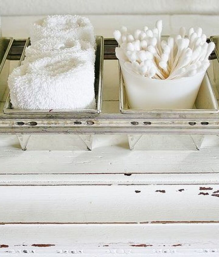 """For the guest bath I used an old factory bread loaf pan to make a """"serving tray"""" of necessities for guests. I set this out with a stack of white fluffy towels when overnight visitors come. Just store the tray until you need it!"""