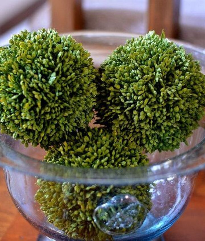 Faux greenery balls in a blue seeded glass bowl.