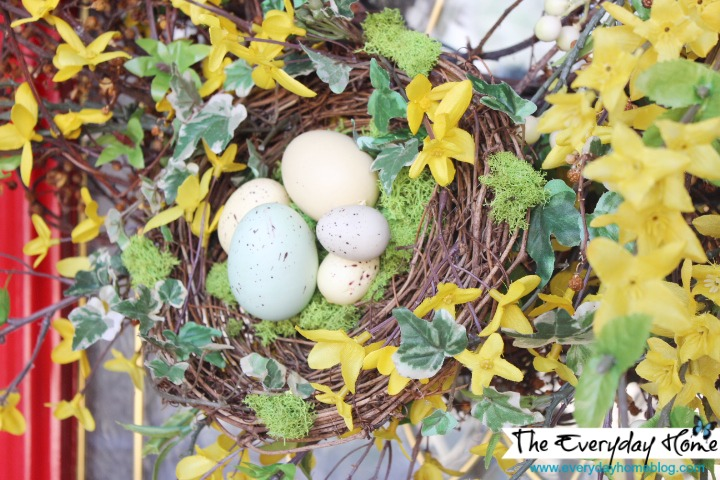 A handmade birds nest filled with speckled eggs accents a forsythia wreath.