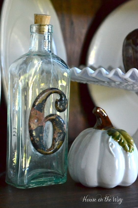 Vintage bottle with white accent pieces in a corner cabinet.
