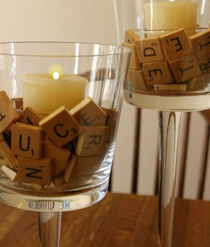Scrabble letter tiles surround a tealight (in a clear container) in a clear footed votive holder.