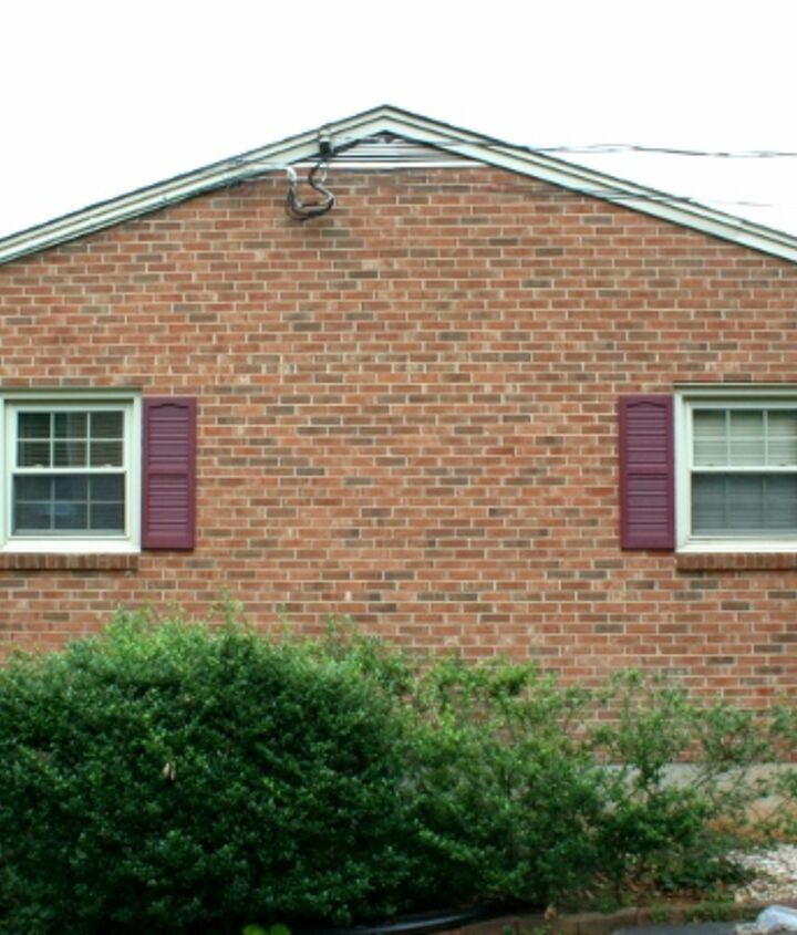 Brick side of the house with the maroon shutters.