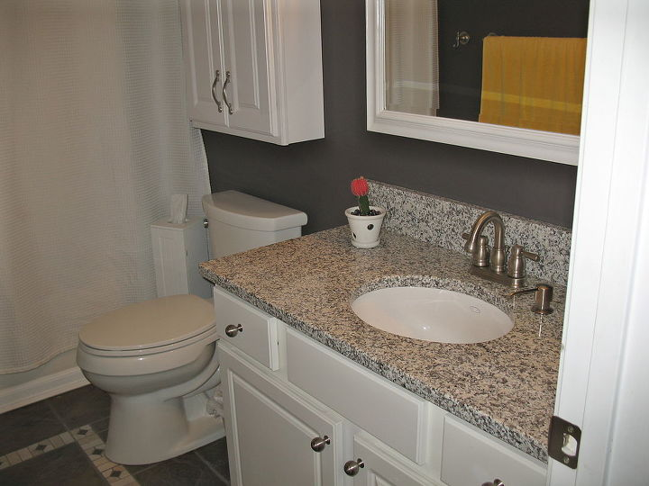 AFTER: New mirror , toilet , sink, granite, knobs, paint on the walls, curtains
