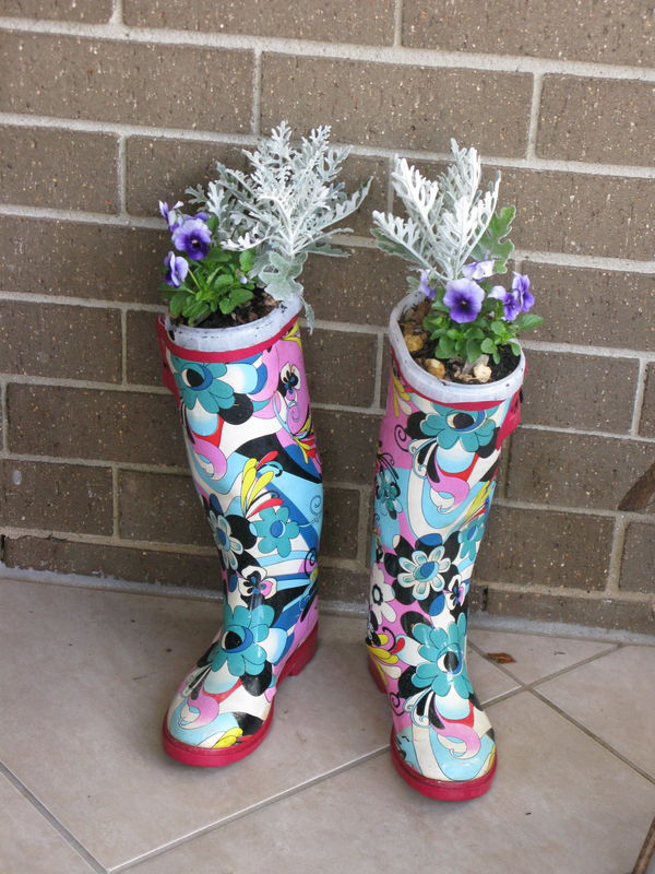 Wellies are weighted down with rocks and in the top is a yoghurt carton that has potting mix and drainage holes.