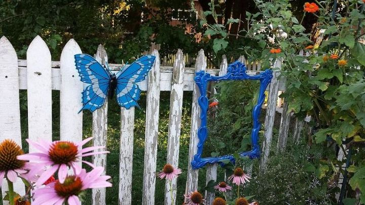 Love this colbalt blue mirror along the white picket fence.