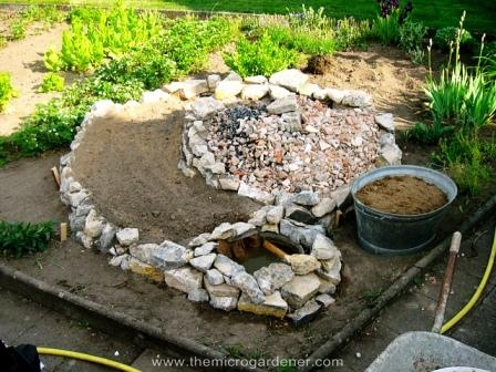 Rocks are laid in a spiral design working upwards to the center and the ramp planting areas are filled with rubble, soil and organic matter.