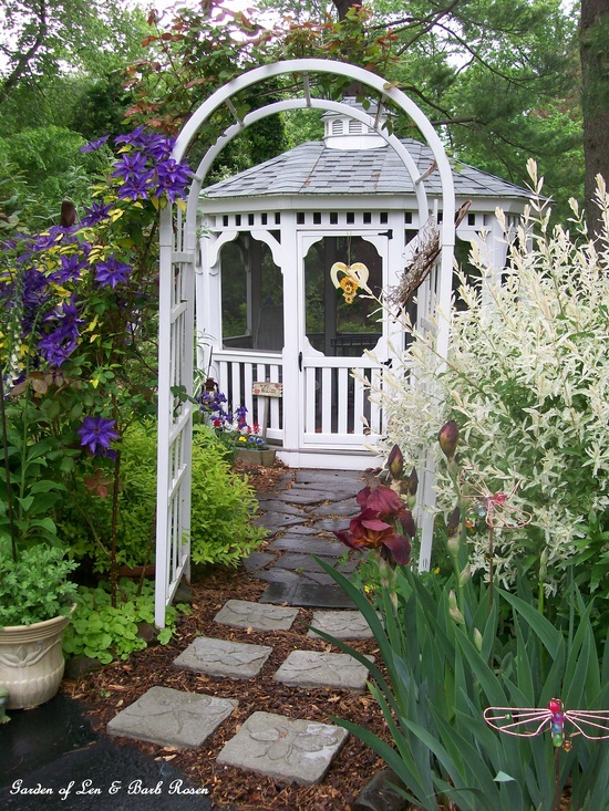 Early May by the gazebo, clematis, iris and variegated willow.