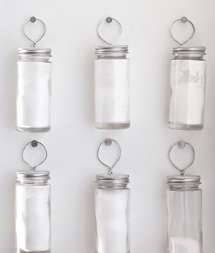 Inexpensive spice jars hung with nails and floral wire.