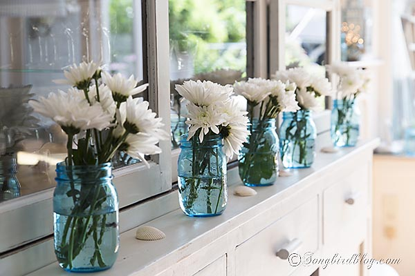 Line Up A Row Of Mason Jars Add Some Flowers And Sprinkle In Shells