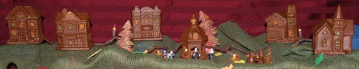 My $1 Store Thanksgiving Village.  It has orange lights through it and I painted everything brown. I love the bleached and blotted with acrylic paint bottle brush trees!