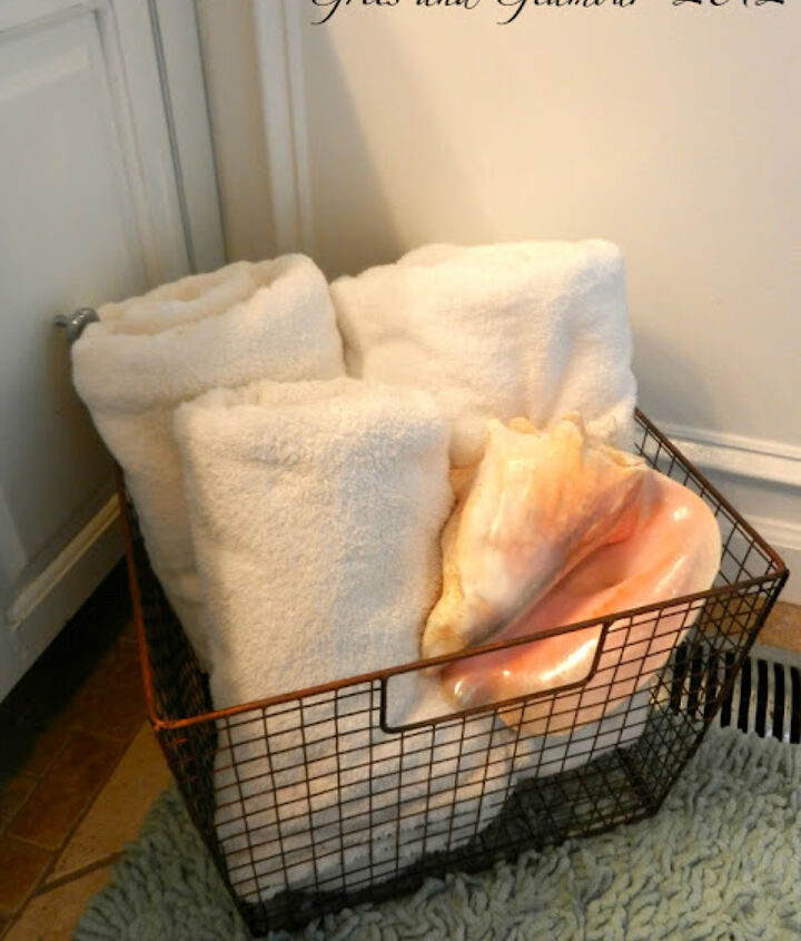 Rolled towels in a wire basket.