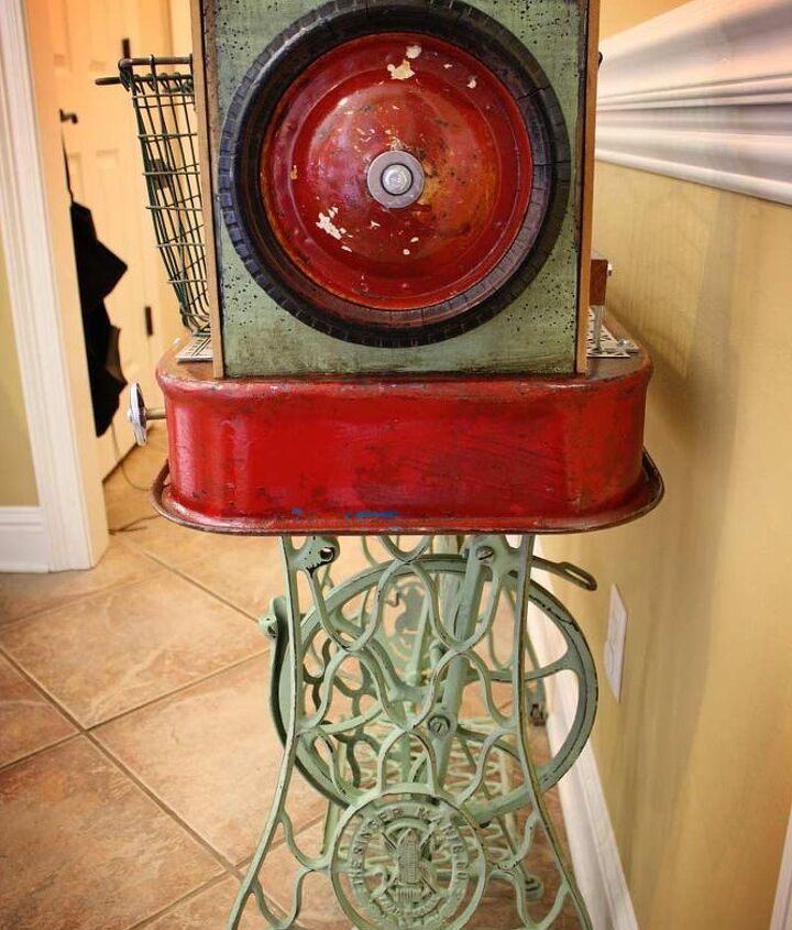 Wheels from the Radio Flyer wagon adorn each side.  Repurposed Red Wagon Sewing Machine Base Storage Table by GadgetSponge