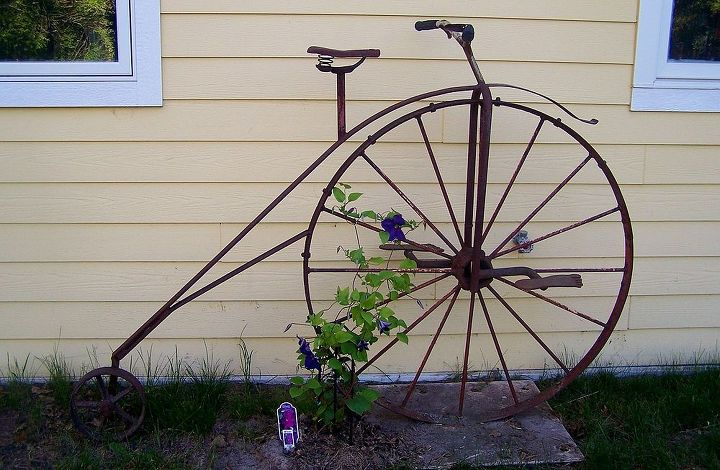 "We have a friend who owned a junkyard. He's also an artist and he ""built"" this vintage bicycle for us out of scrap parts and pieces. Our Clematis is beginning to climb the wheel."