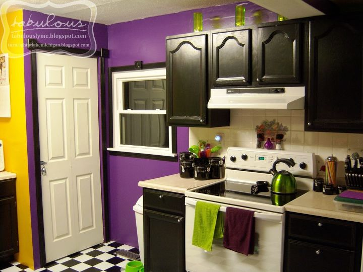 The stove area. We painted all of the cabinets black, adding knobs and lining the inside with a black and white checkerboard contact paper to help protect the interiors. The cabinets are of good quality, we just hated the finish.