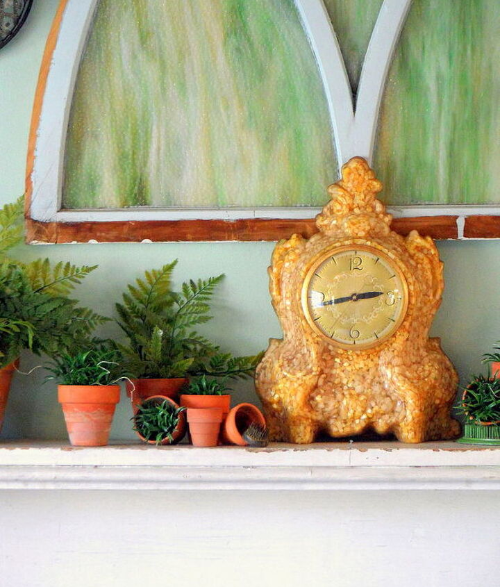 A very French and vintage clock adds a touch of elegance to an otherwise casual display. It also slightly overlaps the window, thereby connecting your wall art to the vignette on the mantle. This keeps your eye moving and makes the whole wall even more cohesive.