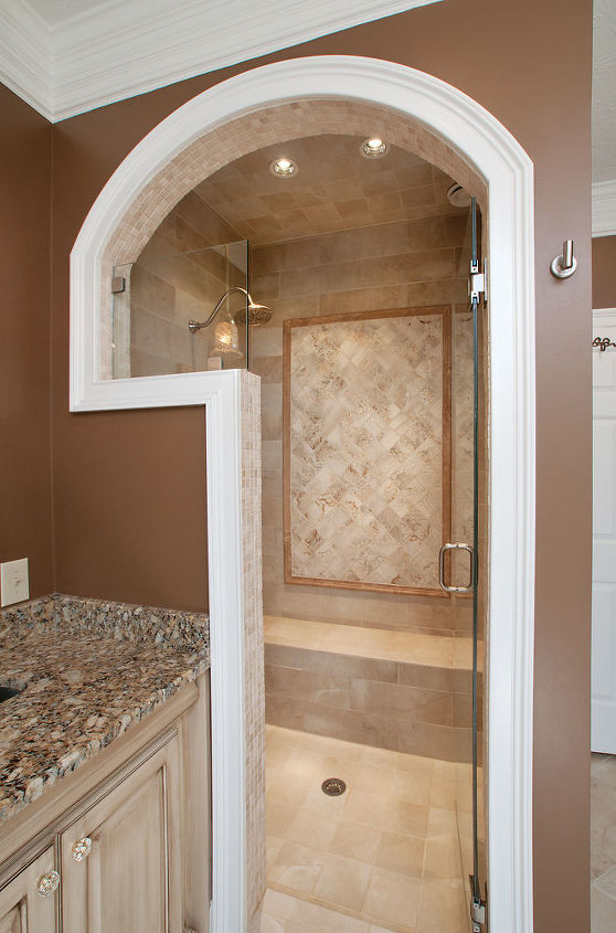 The shower features, two arches, frameless glass enclosure, built-in bench, shower head with separate hand wand on a slider bar, and a heated floor.