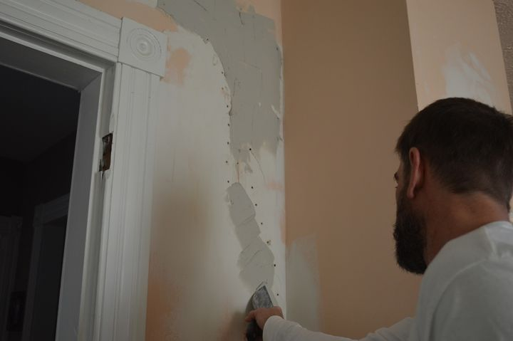 "Using a 4"" drywall knife, fill the crack and holes."
