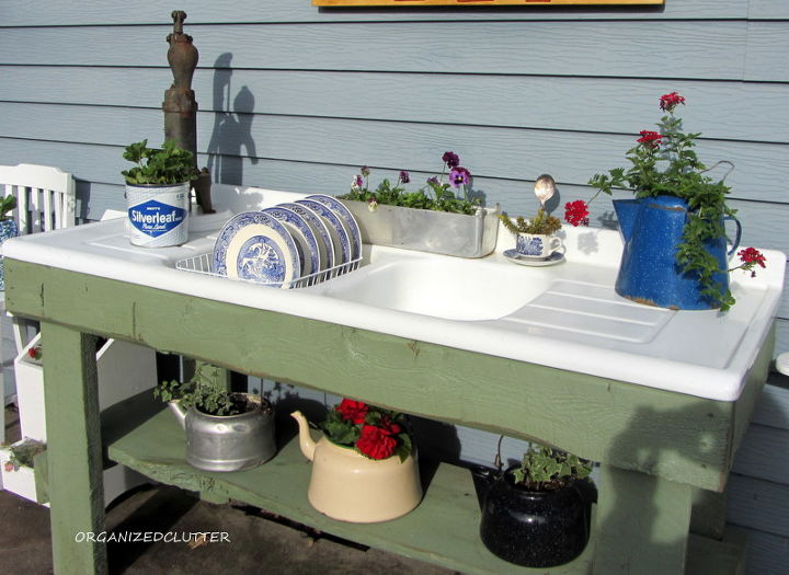 Vintage tea kettles are planted with annuals on the bottom shelf and on the right side drainer.