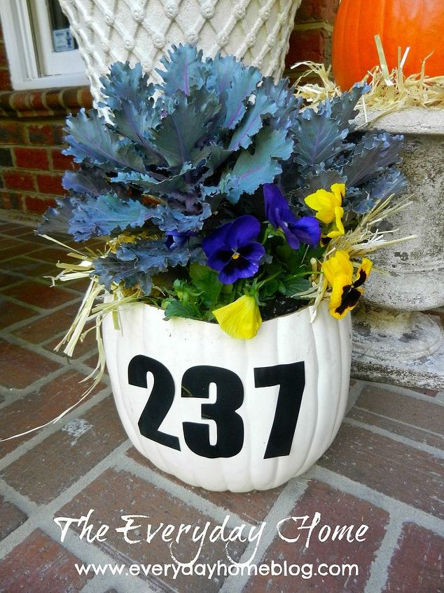 A faux white pumpkin becomes a combination planter and house number sign.