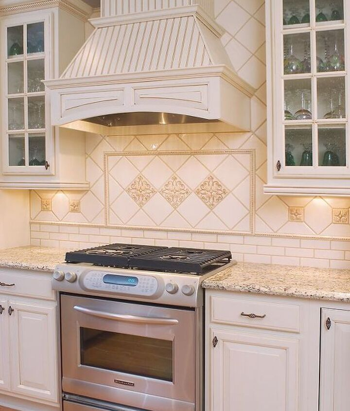 The Focal Point Of The Kitchen (6x6 bone china field tile, iron gate deco's & 3x3 dots) The tile work is so exceptional, it was extended all the way to the top of the cabinets around the hood.