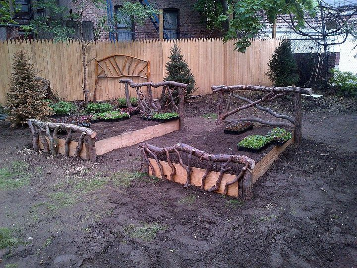 Newly built raised beds with rustic wood headboard and footboard at a garden in the Bronx, New York