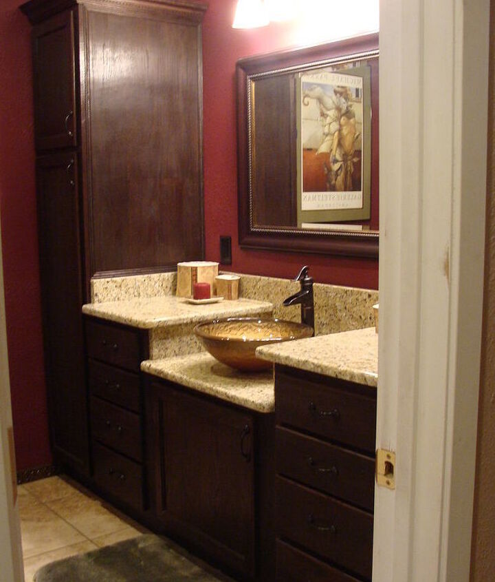 This is the after shot. The only thing we hired done was the granite. My huband custom-did the cabinets himself. We bought unfinished kitchen cabintes from our local Home Depot and changed them to work in the bathroom.