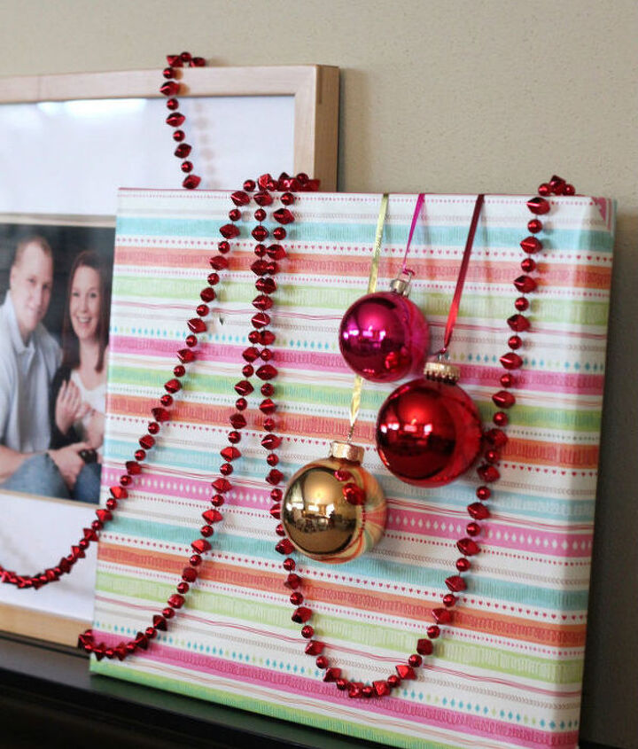Miniature glass ornaments tied with metallic ribbon and taped to the back give your gift-wrapped frames add some whimsy, dimension, and interest.