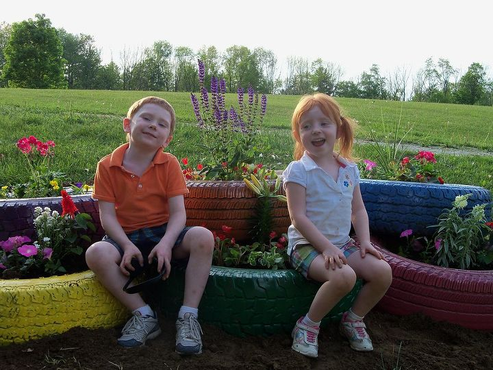 My two children sitting on the new tire garden..