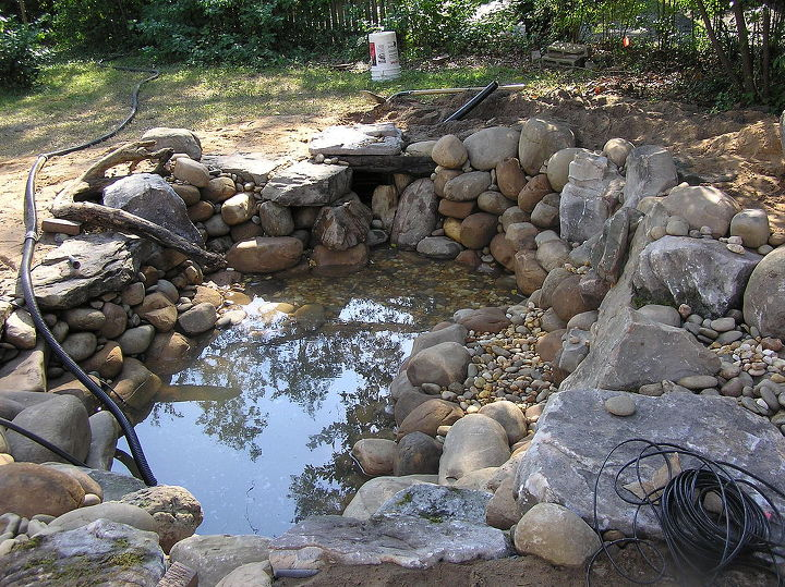 "Next, we gravel all the points in between and around our boulders and rocks.. the gravel ""locks"" the boulders and rock into place as well as it serves as surface area for beneficial bacteria growth. Great for aquatic planting too."