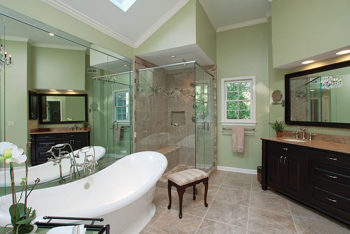 This bathroom features a large double slipper tub, spacious shower stall with bench seat, and dark stained mahogany vanity cabinets with furniture feet.
