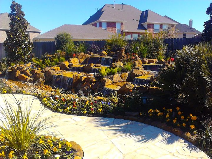 stunning pondless waterfall is the focal point of this backyard near houston texas, landscape, outdoor living, ponds water features, Completed water feature with landscaping and pathway