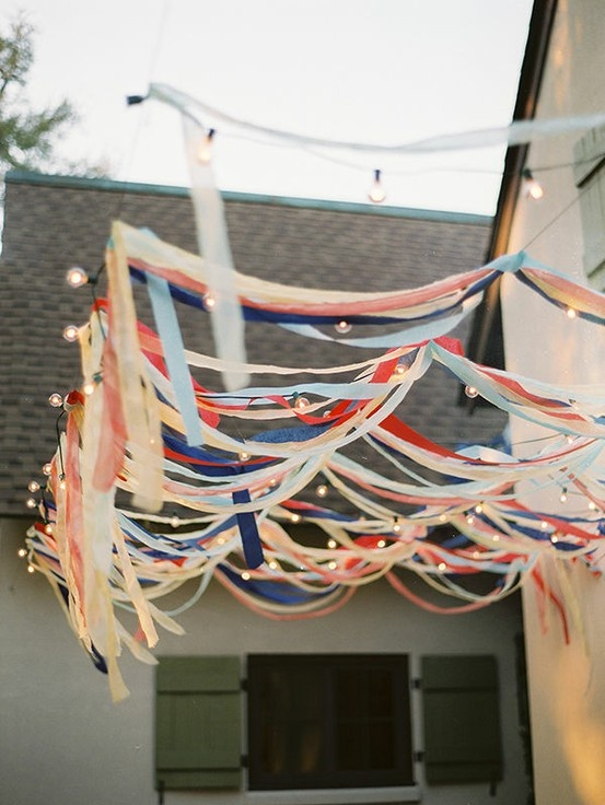 annual memorial day party prep, outdoor living, patriotic decor ideas, seasonal holiday decor, Cheap streamers from the dollar store mixed with some of my infinite mini light collection creates an eye catching accent when guest enter my entertaining area