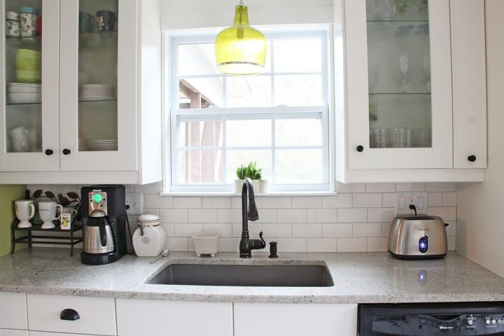 A coffee station to the left of the sink is used every morning.  The sink is a Blanco granite sink in Metallic Gray and the cute green light fixture is from Ballard Designs.