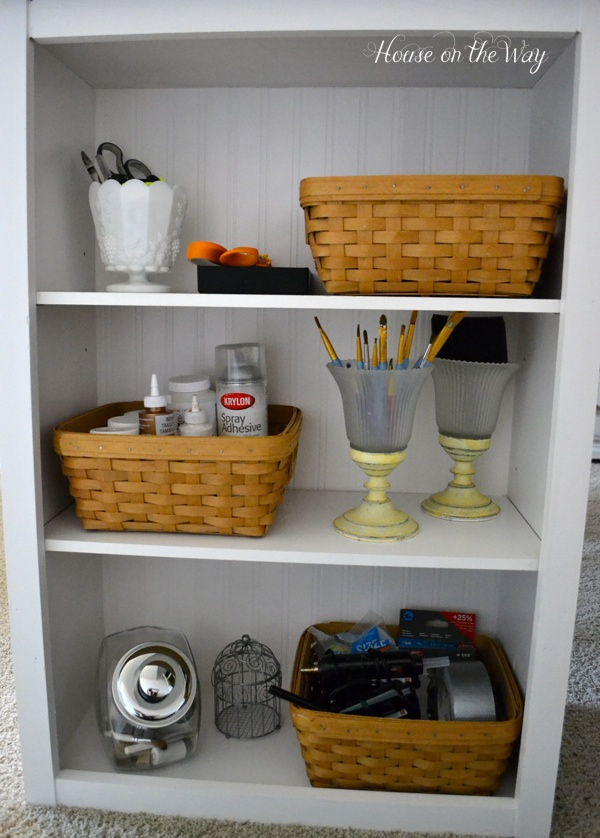 One side of the bookcase holds a variety of supplies.