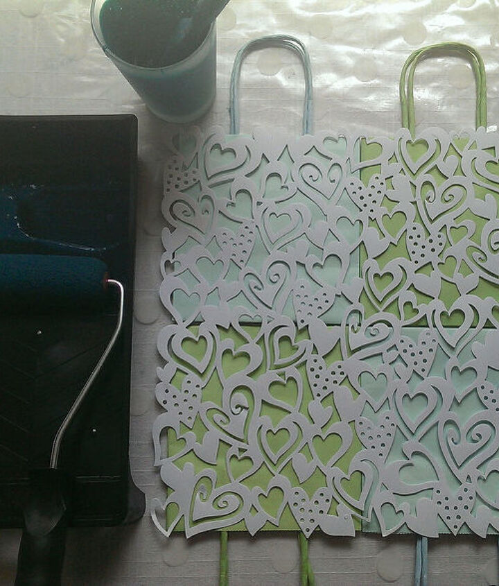 Lay the lace paper pattern over the paper bags, then roller the paint on...