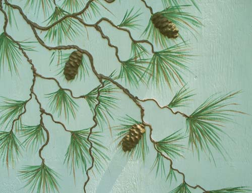 Hand painted and stenciled pine needles give the branches fullness. I then cast our pine cone mold to create real looking pine cones. They were sealed with exterior paint and glued on with construction adhesive.