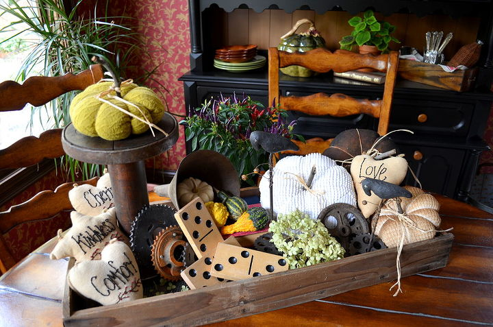Vintage fabric pumpkins, old automotive gear plates, a tin funnel, and a tall wooden spindle are just some of the items used in this kitchen table display.