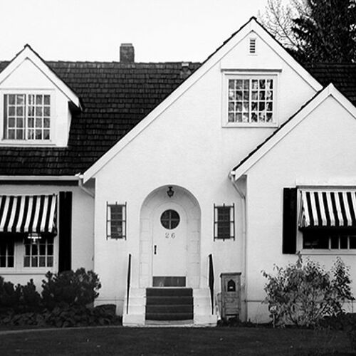 Black & white awnings add visual interest.  A pop of color on the door would be fabulous!