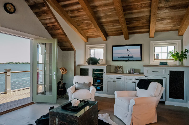 The third floor cathedral ceiling has weathered barn board and exposed rough sawn beams. Custom built cabinetry holds entertainment systems and a small refrigerator. The room opens to an Ipe wood deck with stunning views of the water.