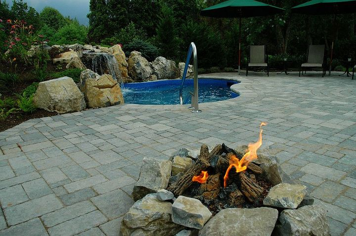Spool with a paver patio, moss rock waterfall, and a gas fire pit. Built on Long Island by www.longislandhottub.com  See more creative photos at http://www.longislandhottub.com/decks-and-patios-portfolio.php
