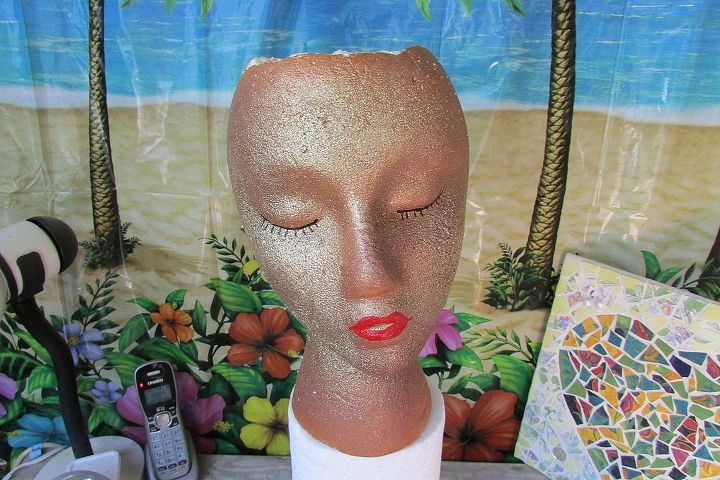Spray paint face, paint eye lashes and lips. Carve out top of head.