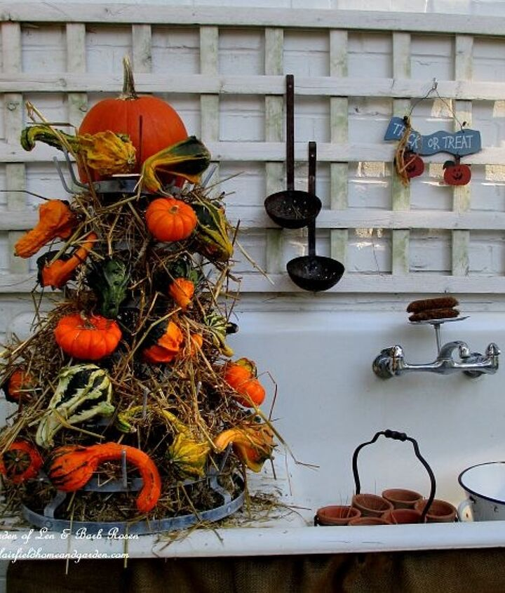 Fall ~ a gourd tower made from hay, gourds and a bottle drying rack with a burlap skirt.