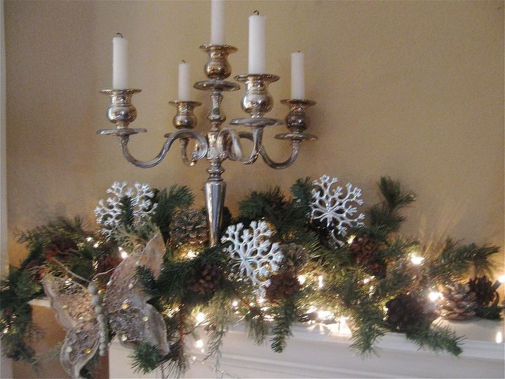 Silver candelabras flank each side of the mantel with greenery, lights, silver snowflakes and whimsical butterflies!