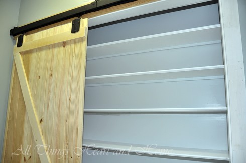 Then added shelves and a barn door...the hardware for the bard door was from a Tractor Store - we just painted it flat black...