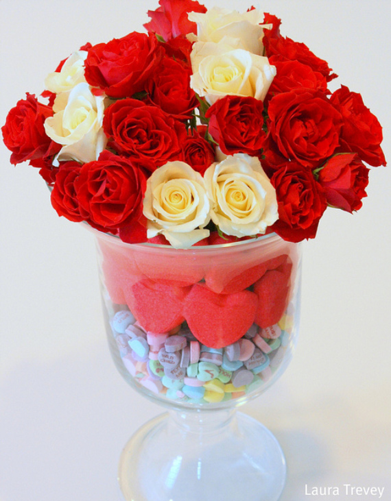 Place a tall and narrow drinking glass inside the large hurricane. Fill the glass with roses and water. Around the sides, pour the sweet-heart candies in the bottom. Place two layers of red heart peeps around the hurricane on top of the candy, voila! A Valentine's Day treat!
