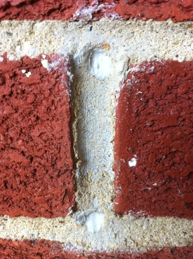 Two chewed holes in brick mortar