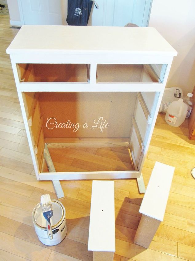 I painted the cabinet frame and two smaller drawers white. I added cute drawer pulls and a curtain made from a fabric scrap.