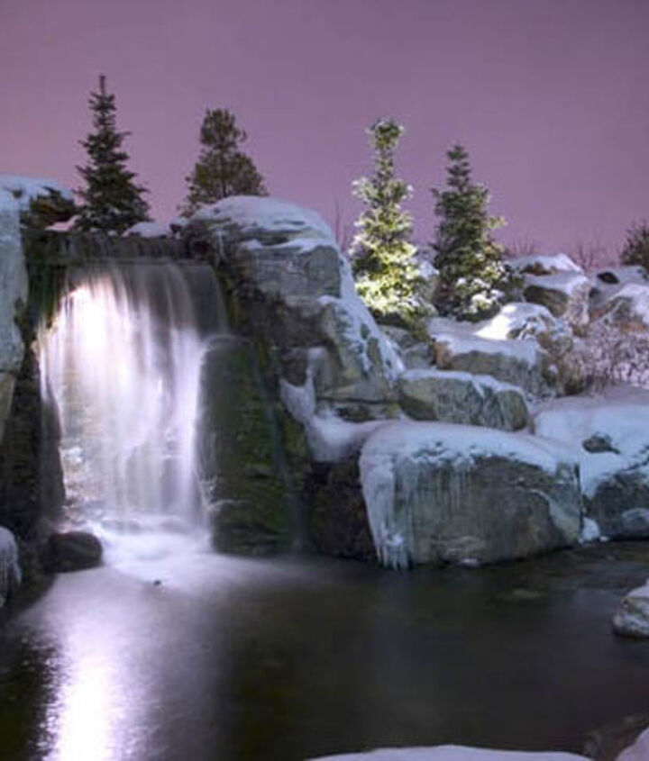 The waterfalls at night with the light shining through the waterfalls.  This water feature is located at Aquascape's corporate headquarters.