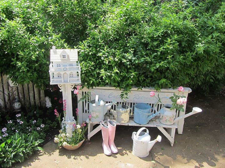 I have been collecting old vintage watering cans and display them in the garden. They are ready for use and also pretty decor.  The back drop to the old bench is an old headboard that I made into a cottage garden back to the bench.